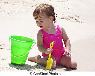 Beach Baby - Curious baby on the beach peering into a bucket