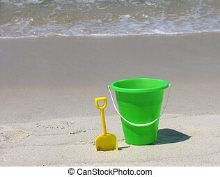 beach background - Green plastic bucket and yellow shovel in...