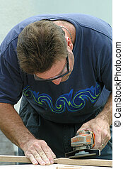 Man Doing Carpentry - A photo of a man, wearing safety...