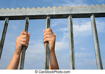 behind bars - hands holding on to bars