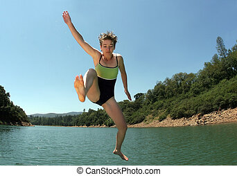 Jumping in the lake - Young woman jumping in the lake