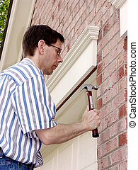 Home Improvement (5) - Man wearing glasses is pounding with...