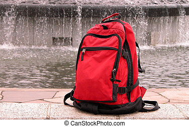 Travel Bag - A red backpack in a park, fountain background