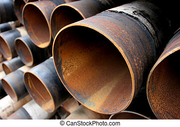 large rusting steel pipes - closeup of a pile of large and...