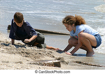 Making Sandcastles - A boy and girl building a sand castle...