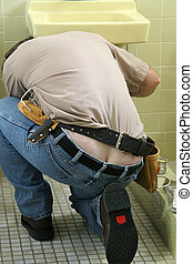 Plumber Crack - A plumber bending over to fix a sink. His...