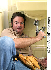 Plumber Working - A plumber using a wrench to tighten a pipe...