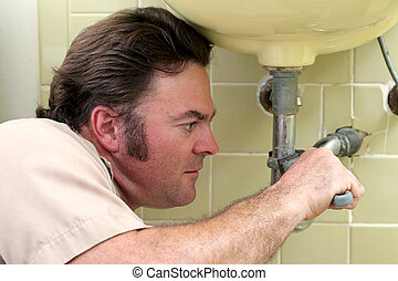Plumber Tighten Pipe - A closeup of a plumber using a wrench...