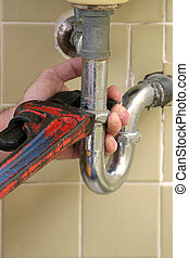 Plumber Pipe Wrench - A closeup of a plumber using a pipe...
