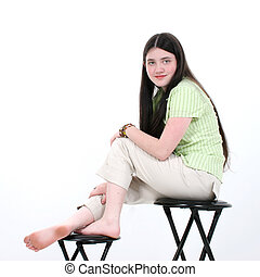 Beautiful Tween Girl Sitting On Stool in Casual Clothes Shot...