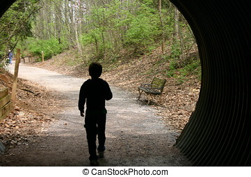 Out of the darkness - Boy walking into the light from the...