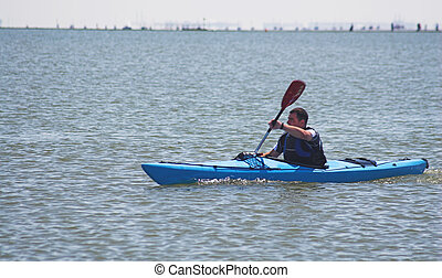 Canoe - A canoeist paddles his canoe at sea