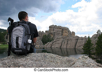 Man overlook - Man with backpack overlooking a lake and...