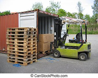 Truck at container - A truck with a driver lifting a pallet...