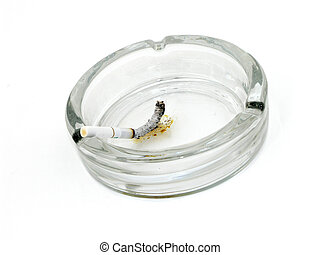 Smoldering Butt - Burning cigarette in glass ash tray over...