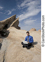 Business on the go - Man sitting on a hilltop conducting...