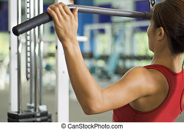 Lat Pulldown 3 - A woman demonstrates a lat pulldown...
