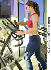 Stepper - A woman does some cardio exercise on a step...