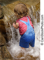 Baby water play - Baby in overalls playing in water