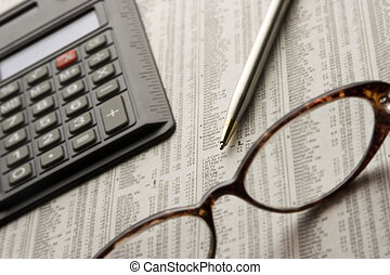 Perusing Stocks - Paper, glasses, pen, and calculator, items...