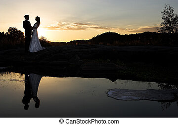 sunset bride - bride and groom next to river at sunset