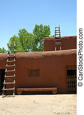 Adobe - Hand hewn ladders lean against ancient adobe ranch...