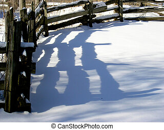 Wooden fence in the winter time and its shadow over the snow...