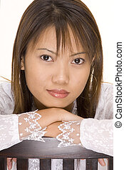 Girl In White 5 - A pretty young asian girl rests her head...