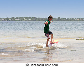 Boy Surfing - A boy skim boarding/surfing at the beach.
