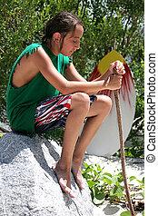 Surfer Boy Resting - A boy sitting on a rock at the beach...