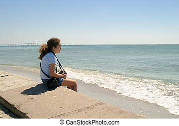 Solitude - A teenaged girl sitting by the sea shore.