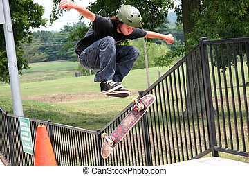 Flying Skateboarder - Skateboarder jumping cone and flipping...