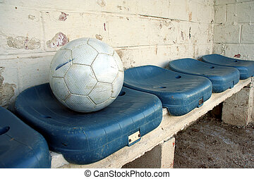 ball on seats - a soccer ball on blue dug-out seats