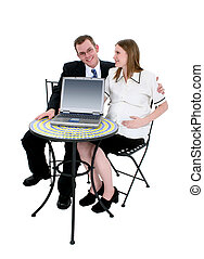 Image Request - Pregnant couple sitting at bistro table with...