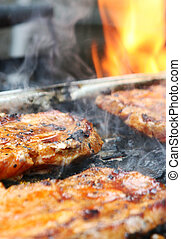 Barbeque 2 - Delicious steaks sizzling on a grill and fire...