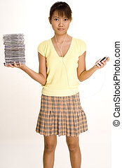 Listening to Music - A young asian girl holds a stack of CDs...