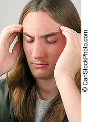 Deep Concentration - A young man massaging his temples like...
