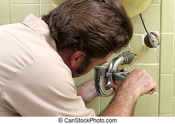 Tightening Plumbing - A plumber busy tightenting a pipe....