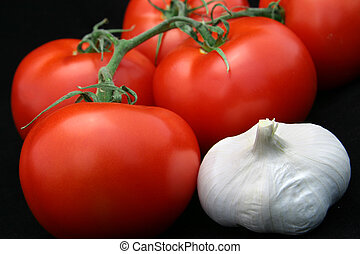 Tomatoes & Garlic - Ripe, red tomatoes and garlic against a...