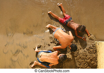 Sand Diggers - Three boys digging in the sand from above