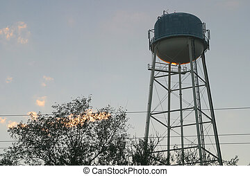 Water Tower Sunset - A water tower, silhoetted against an...