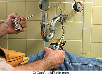 Soldering Pipe - A plumber using a welding torch to solder...