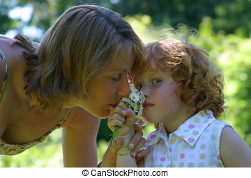 Mother and daughter - Mother and child smelling the daisies