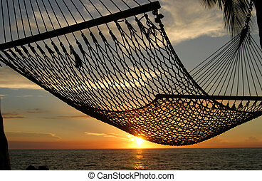 Catching the Sunset - A sunset is seen through a hammock on...