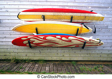 surfboards - three worn surfboards hanging on the house