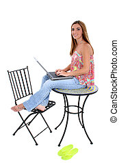 Woman Computer - Young woman barefoot in jeans and summer...