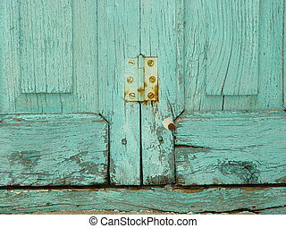 Rusty hinge on turquoise, weather-beaten window shutter on...