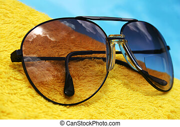 Aviator Glasses - Aviator sunglasses on yellow towel by the...
