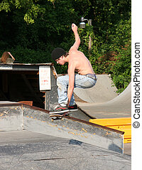 Teen Skater Grabbing Board - Male teen skateboarder grabbing...