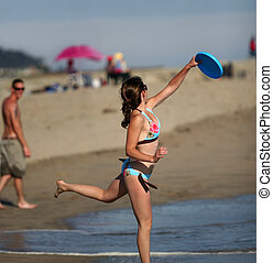 Girl playing frisbee on the beach